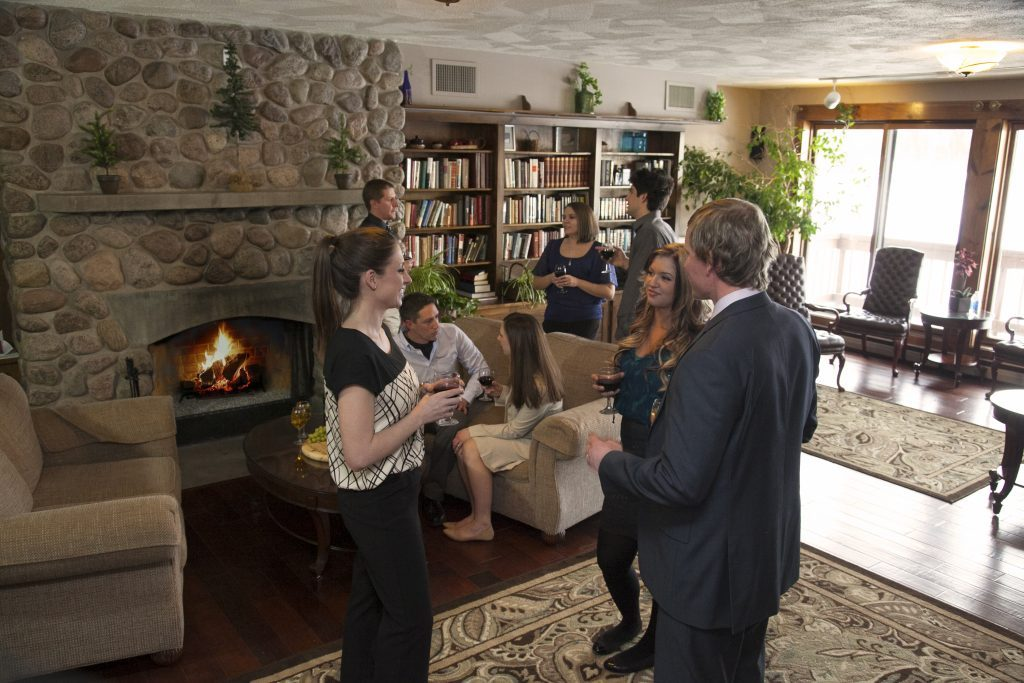 Guests in business wear mingling infant of a roaring fireplace