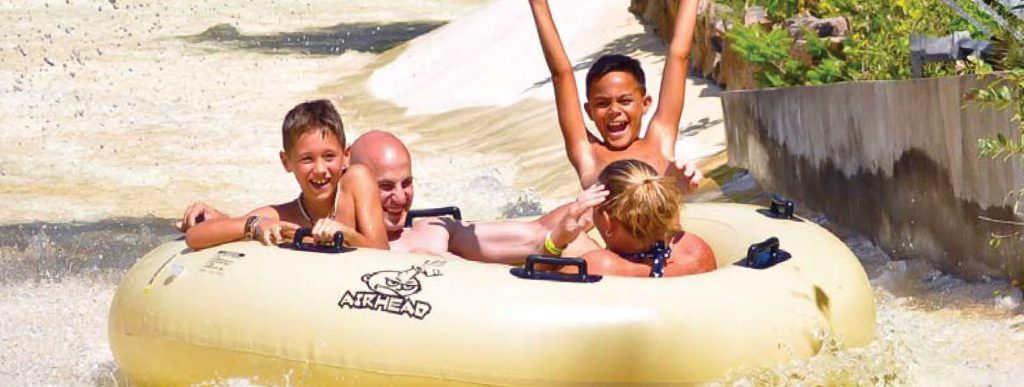 Image of a family going down the water ride in a big yellow tube. Theres a mom and dad along with two young boys who are smiling and facing the camera, one even has his arms in the air.