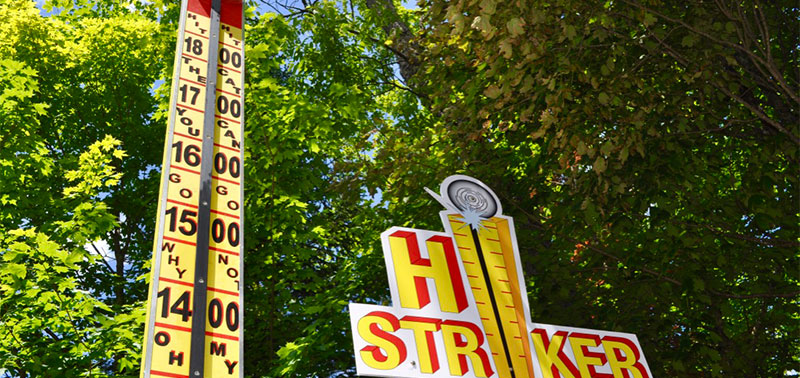"An image of the Hi-Striker arcade game with trees in the background. The yellow and red sign reads ""HI STRIKER"" and the meter next to it increases in values from 14 to 18."