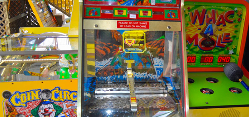 "Image of three colorful arcade games at Enchanted Forest Water Safari. The game to the left is called ""Coin Circle"" and is a yellow machine with an image of a clown on it. The machine in the center has mountain imagery and coins in it. The game on the right is a green machine with a hammer, and is called ""Whac A Mole""."