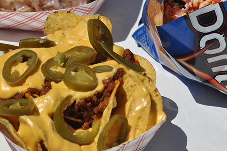 A close up image of nachos with meat and jalapenos on them with an open blue bag of Doritos to the right.