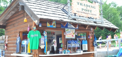 Image of the storefront of the Trading post. You can see a bright green t-shirt hanging up, and then open windows for guests to order from looking into the shop.