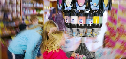 Image that is blurred on the sides but you can clearly tell its two girls in the candy shop looking at all the candy options.