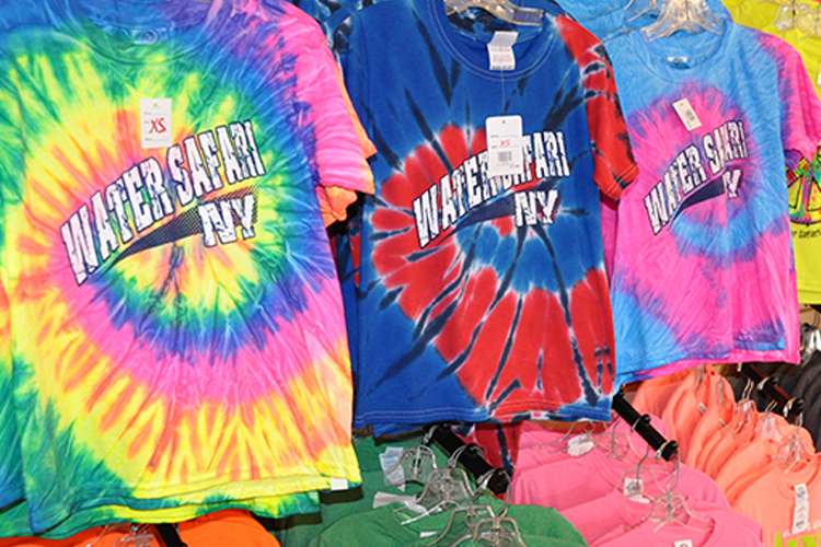 "An image of racks of colorful tie-dye t-shirts in the gift shop that read ""WATER SAFARI NY""."
