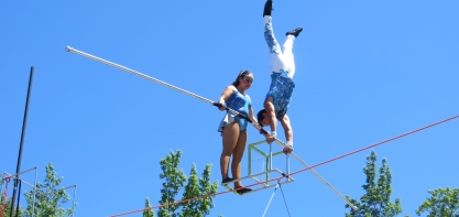 Image of the Ayala Family during their family circus act. One man is balancing on a box on a tight rope while doing a headstand while a girl is walking the tightrope holding onto a stick.