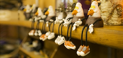 Image of souvenirs at the Woodsy souvenir shop. Little trinkets sitting one a shelf with their legs dangling off.