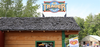 Image of the Island Trader gift shop. The sign is on the roof of the building, it goes with the red, green and yellow theme seen at other places in the park.