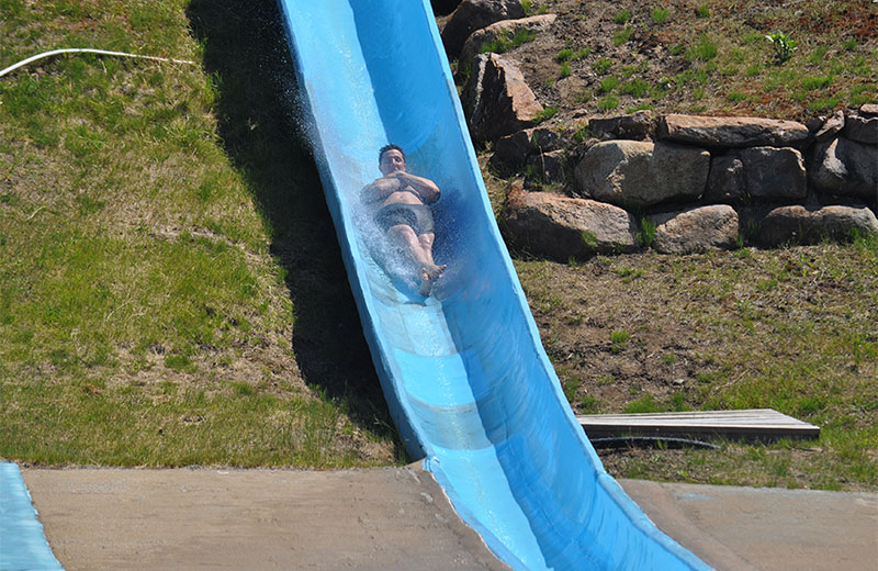 An image of a man lying back with his arms crossed over his chest and feet crossed going down the Killermanajaro water slide. The slide is blue and there are grass and rocks behind it.