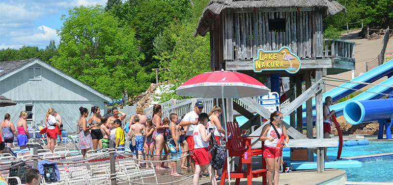 "Image of Lake Nakura, a water attraction where you try to cross the pool holding onto a rope. On the left in the image is a crowd of people with beach chairs and to the right is a lifeguard stand with four lifeguards, a wooden structure with a blue and yellow sign reading 'Lake Nakura"", and the pool with waterslides visible behind it."