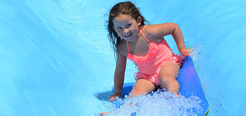 Image of a little girl in a pink bathing suit as she sits on a mat and goes down the pygmy slides