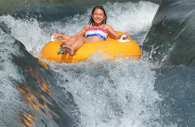 Image of a girl smiling while going down the raging rapids on a yellow tube.