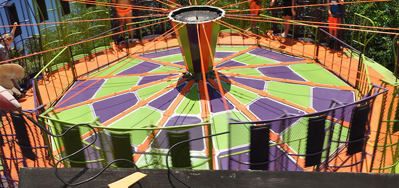 An image of a ride full of green, purple and orange. Spinning people around on a tilt called the Round-Up.