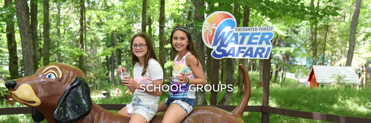 An image of two young girls holding Dippin' Dots and sitting on a large brown statue of a dog. Behind them are green trees and a pole with the Enchanted Forest Water Safari logo on it.