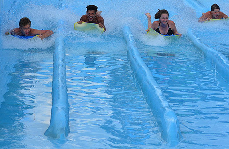 Image of four people sliding down the water slides face first on a mat.