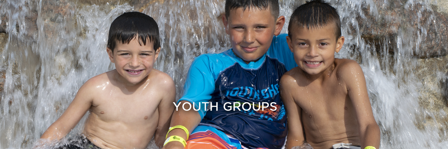 "An image of three young boys in bathing suits smiling as water splashes behind them. There is white text centered at the bottom of the image that reads ""Youth Groups""."
