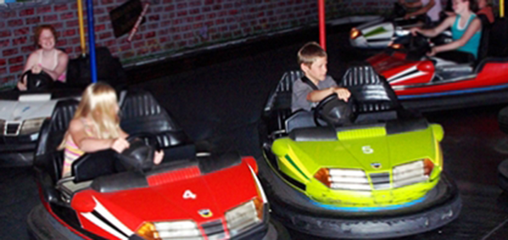 Image of three kids playing on the bumper car rides. One girl is driving a red car trying to hit the boy next to her who is hitting the green car.