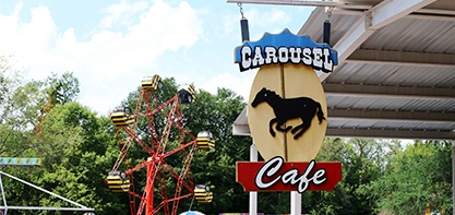 Sign for the Carousel Cafe, the sign has carousel in blue then a black image of a horse and then under in red it says cafe.
