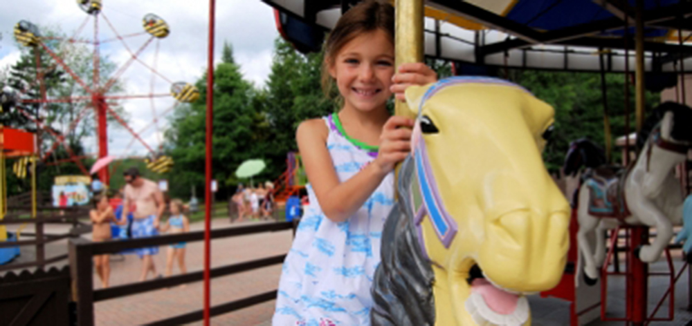 Image of you young girl smiling at the camera as she rides a yellow horse on the carousel.