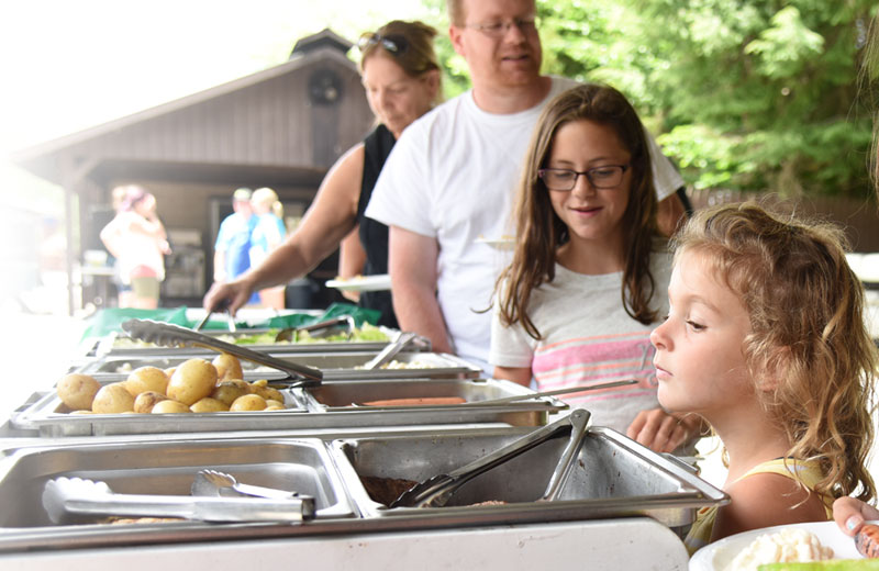 An image of a family getting lunch at a picnic buffet. The mother, father and oldest daughter are smiling and getting food and the youngest daughter in the lower right corner is peering into the pans of food.
