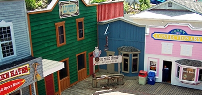 Image off the buildings in Dawson City. The buildings look like they are straight from a western film. The buildings are blue, green and pink.