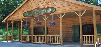 Photo of the log cabin Enchanted Memories Museum. The museum has a porch with purple hanging flowers and green doors leading inside.
