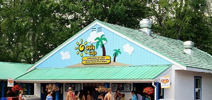 Image of the Oasis Cafe. It's an image of the top half of the building. The sign is a painted picture of an island with palm trees and the sun that reads Oasis Cafe.