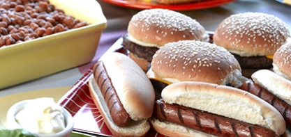 An image of flame-grilled hamburgers and hot dogs in buns.
