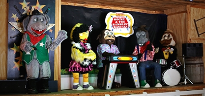 Image of the Rocky & the Ramblin' Rascals. A performing band, the band is centerstage. The characters look like puppet animals. there is a cow, donkey and bird