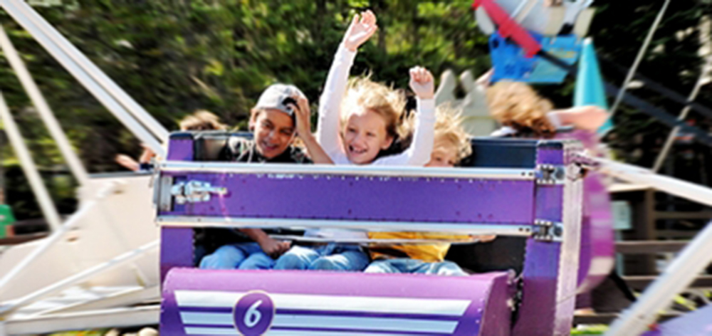 Image of three children on the scrambler ride. There is a little girl in the middle with her hands in the air and a smile on her face.
