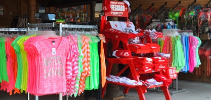 image of the Tiki Tim's Longboard Surf Shop. Image off different colors shirts on display along with lifeguard gear available for guests to buy.