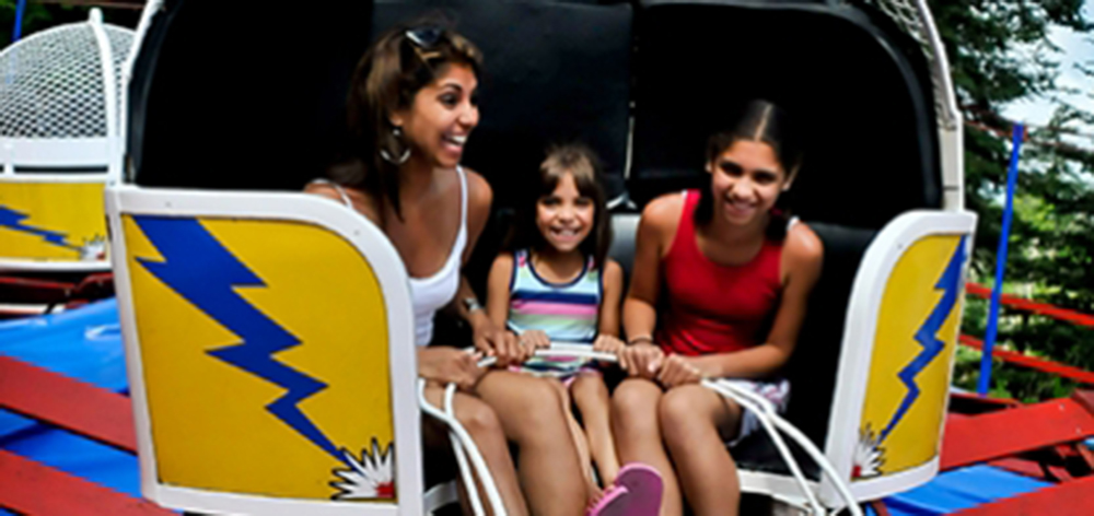 Image of a mother and her two daughters smiling as they ride the tilt-o-whirl.