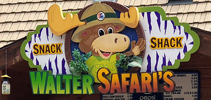 Image of a storefront sign depicting a cartoon moose wearing a hat and green shirt waving with the text Walter Safari's Snack Shack.