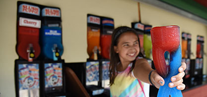 Image of a girl smiling and holding a slushy out to the camera