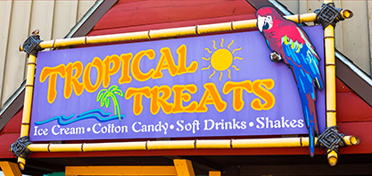 Image of the Tropical Treats Sign with a parrot on the sign. The sign says they offer Ice Cream, Cotton Candy, Soft Drinks and Shakes