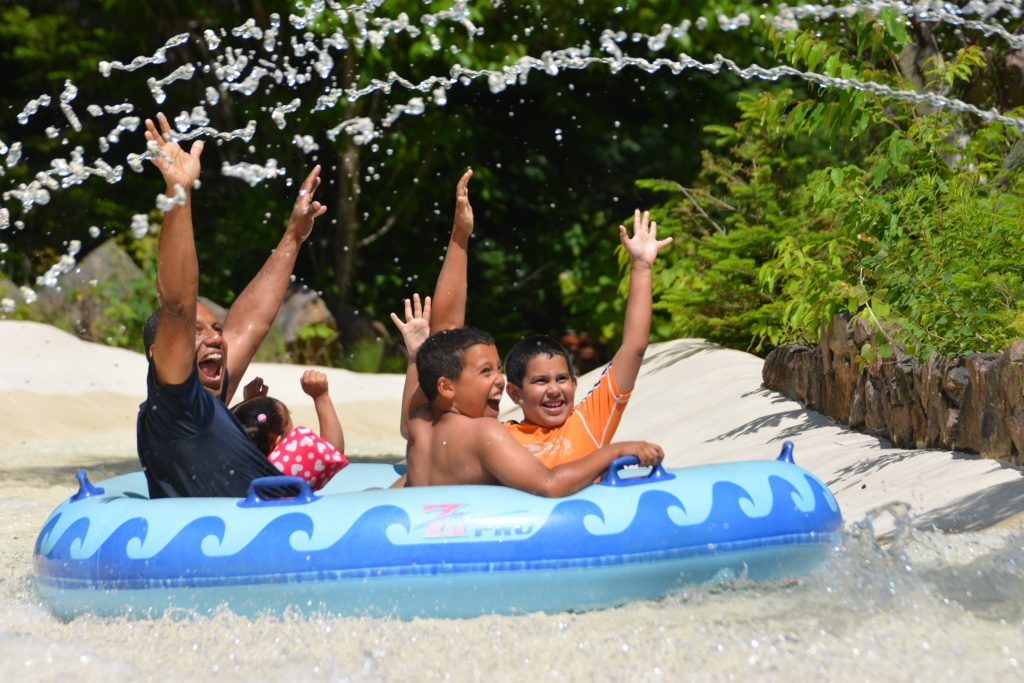A family getting sprayed with water on the Amazon ride. Their hands are up and all four of them are laughing and smiling