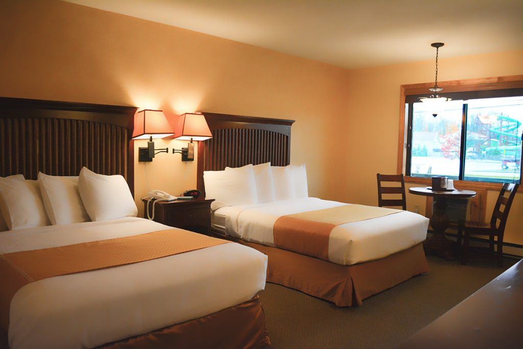 An image of the Standard Double Room at the Water's Edge Inn. There are two beds with white and gold bedding with a table and two lamps between them, and a brown table with two chairs next to the window. Enchanted Forest Water Safari can be seen out the window.