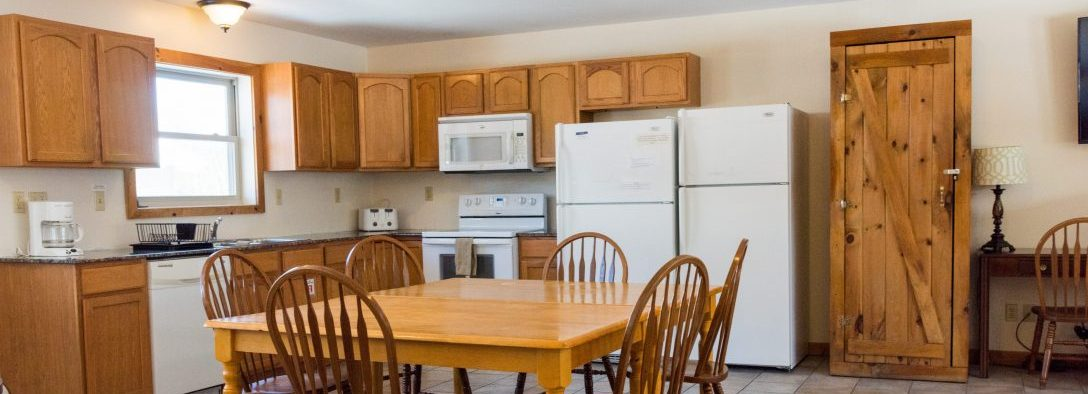 Image of the kitchen in the vacation house. The appliances are all white with tiled floor. Theres a large kitchen table in the kitchen that can seat 6