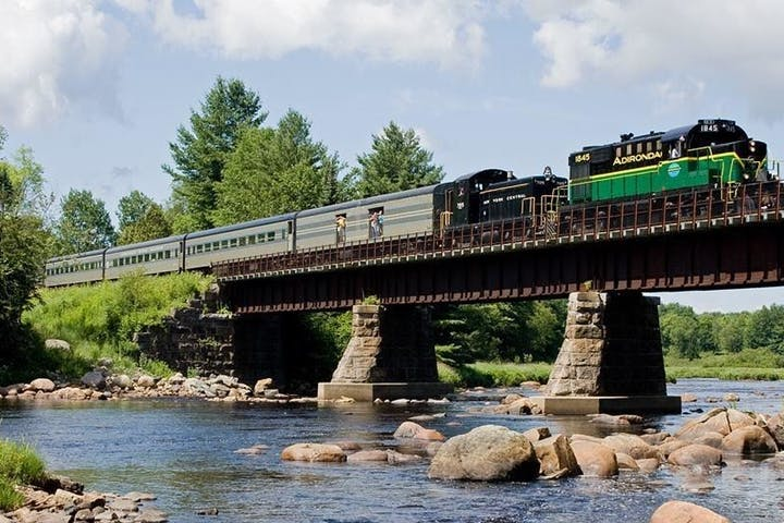 The Adirondack scenic railroad on a bridge over water with boulders sticking out on a sunny day with green trees in the background