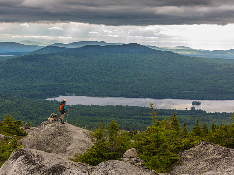 A hiker on top of bald mountain looking out at the lake and trees with the mountains in the distance